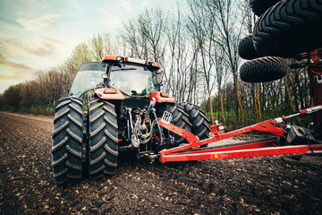 Fototapete - tractor with the sowing equipment rides on the ground in the field in the spring
