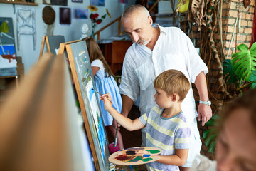Portrait of senior teacher helping little boy painting picture in art studio standing by easel, copy space