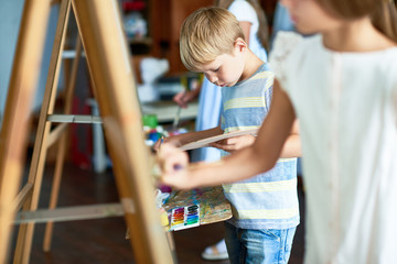 Portrait of cute little boy painting on easel amid group of children in art class, copy space