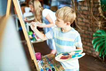 Side view  portrait of blonde little boy painting on easel enjoying art class with other children in background