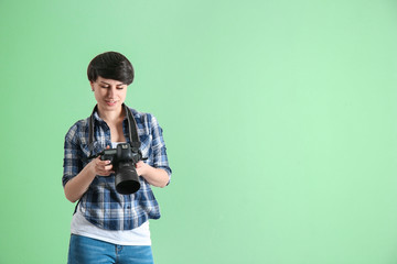 Young female photographer with camera on color background
