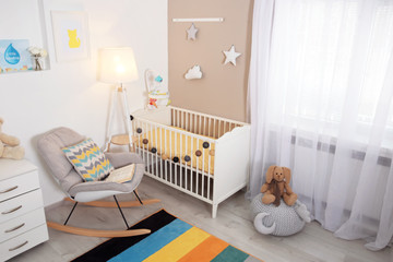 Cozy baby room interior with crib and rocking chair