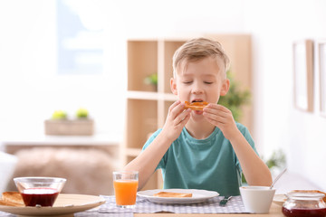 Cute little boy eating tasty toasted bread with jam at table