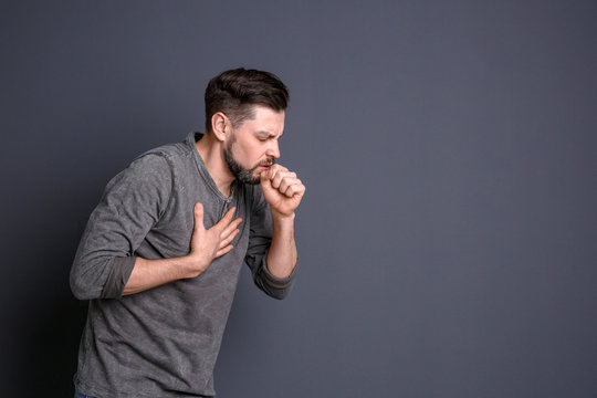 Mature man coughing on color background