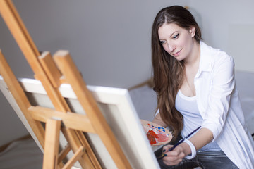 Young beautiful woman painting on canvas, mixing colors on  a color palette, enjoying her hobby or occupation