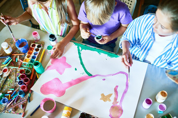 High angle view at  three children painting pictures with watercolors working together in art studio, copy space