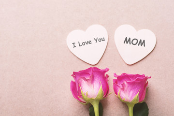 Pink roses and heart shape with I Love You Mom text in mother's day
