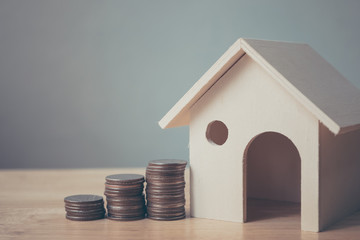 Property investment and house mortgage financial concept, House model and coin money on table for finance and banking