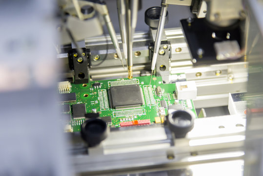 The microchip on the main board in the assembly line in the light blue scene with lighting effect, computer part manufacturing concept.