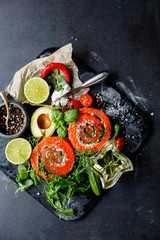 Delicious Salmon rolls, goats cheese in paper with knife, aromatic herbs, spices  on old black stone background, clean eating, healthy food, diet or cooking concept, top view, overhead, flat lay