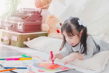 Happy Asian little cute girl drawing and painting color on notebook in a white room background.
