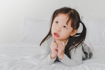A little cute girl lying down on the bed looking up and thinking in the white bedroom.