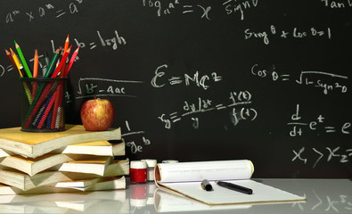 Books are stacked on table with mathematical equations on blackboard