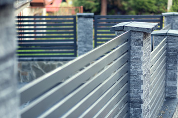 Modern fence with stone pillars and metal filling. Shallow depth of field with copy space.
