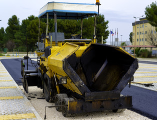 Tracked paver laying fresh asphalt pavement on top of the gravel base during road construction