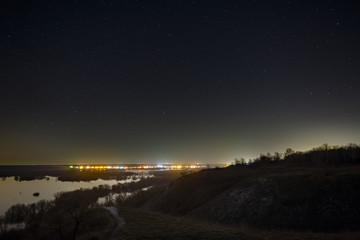 Starry sky at night over the city and forest. Landscape with a long exposure.