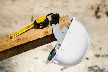 Safety helmet and measure tape on the board