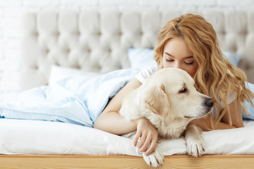 Beautiful teen girl with golden retriever dog in a bed