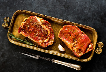 Wall Mural - Two raw beef steaks  in marinade of spices and herbs and a metal fork for meat