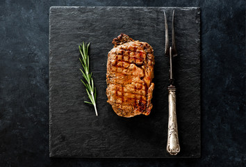Steak Ribeye with rosemary on a black slate board and a metal fork for meat