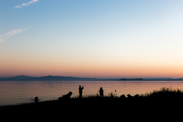 Silhouettes of a couple on a lake shore, taking photos of sunset