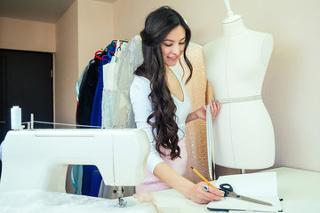 portrait of a beautiful seamstress brunette with long hair working with a sewing machine. tailor creates a collection of outfits . young woman fashion designer measuring tape white tailor mannequin