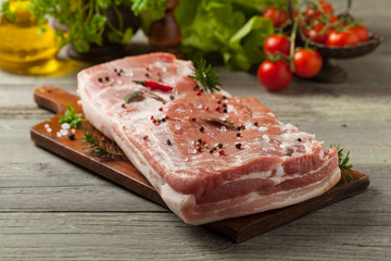 Raw bacon in whole on wooden background.