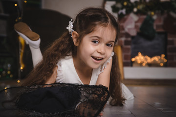 Very nice charming little girl brunette in white dress in the room decorated for Christmas and New year