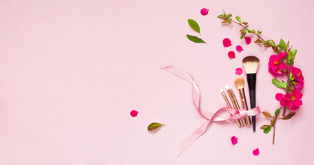 Various brushes for make-up and pink spring flowers on a pink pastel background top view with copy space. Makeup Accessories Top Flat Lay