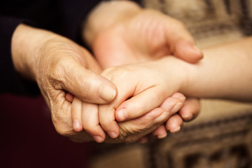 Grandmother holding the grand-daughter's hand