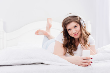 portrait of young woman in pajama and headphones with smartphone lying on bed at home