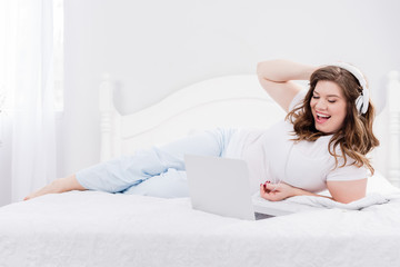 young woman in headphones using laptop on bed at home