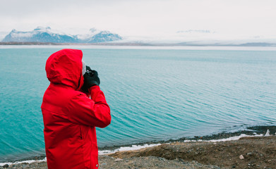 Nature travel photographer, person in red jacket taking photo of river in Iceland