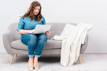 young woman using laptop on sofa at home