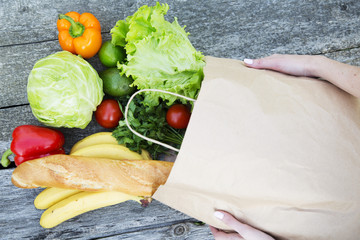 Woman holding full paper bag of healthy products on wooden table. From above.