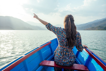 Young woman tourist in a beautiful dress is swimming on the lake by boat and enjoy the scenery of the mountains. the concept of outdoor activities. back view