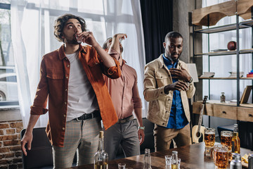 multiethnic male friends drinking tequila while partying together indoors