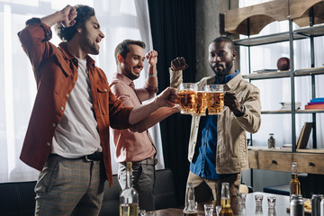 Poster de jardin Bar excited male friends clinking beer glasses while partying together