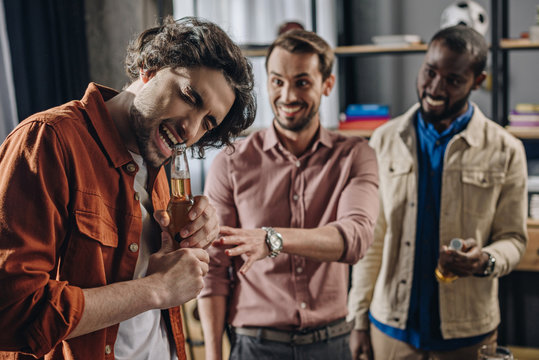 smiling multiethnic men looking at friend opening beer bottle with teeth