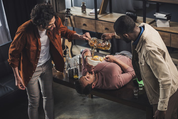 multiethnic friends pouring beer in funnel and man drinking while lying on table