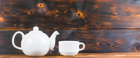 tea cup and pot on rustic wooden table, panoramic shot
