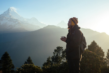 A young man with a red beard and a backpack in the mountains holds a cup with a hot drink in his hands. the concept of active recreation and tourism in the mountains. Nepal in the spring