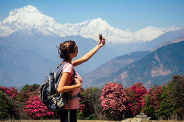 beautiful and young girl doing selfie and photographing the landscape in trekking in the mountains. the concept of active recreation and tourism in the mountains. trekking in Nepal Himalayas