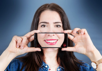 woman with smartphone that takes a picture of her smile