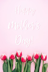 Mother's day greeting card with tulips on pink background. Top view.