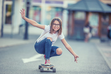 Cut young skater girl riding on her longboard in the city