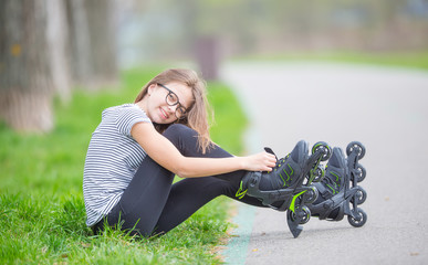 Cute young going rollerblading sitting in grass putting on inline skates