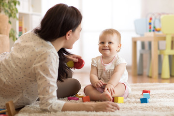 Nanny or babysitter looks after kid toddler. Baby girl playing with educational toys in nursery. Child having fun with colorful different toys at home.