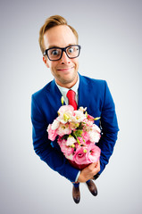 Businessman in glasses, suit and red tie, holding bouquet of flowers