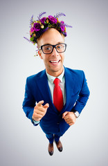 Businessman in glasses, suit, red tie and wreath of wildflowers